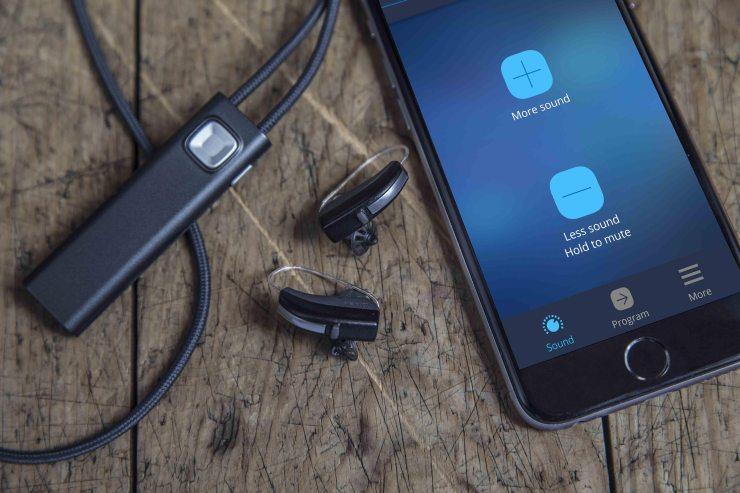 com-dex next to hearing aids and iphone with com dex app